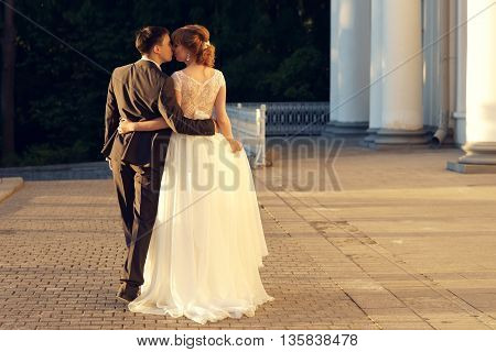Young just married caucasian couple walking away in sunset lightning