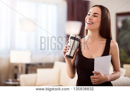 Today is a good day. Beautiful delighted young woman looking aside while holding a clean sheet of paper and a thermo mug