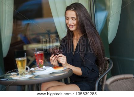 Portrait of a cute brunette  smiling woman sitting in a cafe with a cap of coffee ad cake.