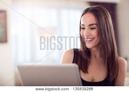 Working time. Close up of an adorable elegant young woman working on the computer and looking at the screen