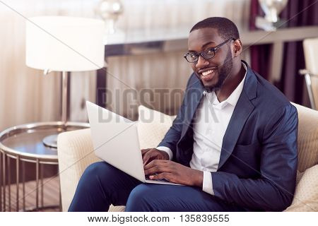 White collar. Joyful elegant young afro American man looking at the camera while using his laptop and sitting on the couch