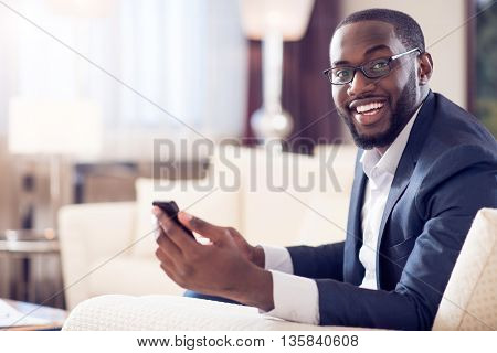Nice time. Pleasant mature afro American man looking at camera while holding a smart phone and sitting on the couch