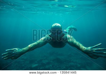 man swim underwater sea dive in clear water