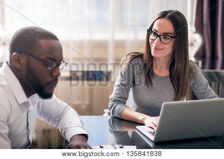 Nice company. Pretty smiling business woman looking at her pensive colleague while sitting at the table in front of a laptop