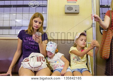 Moscow Russia - August 10 2015: The situation in the train of the Moscow Metro the mother looks at the phone the youngest daughter is asleep the eldest of boredom clinging to the railing