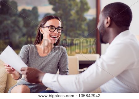 We enjoy working together. Pleasant business woman with wide smile looking at her afro American colleague while holding the same paper with him