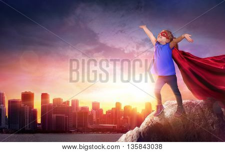 Superhero Child With Cityscape To Sunset - Power concept