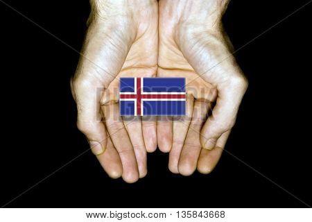 Flag Of Iceland In Hands On Black Background