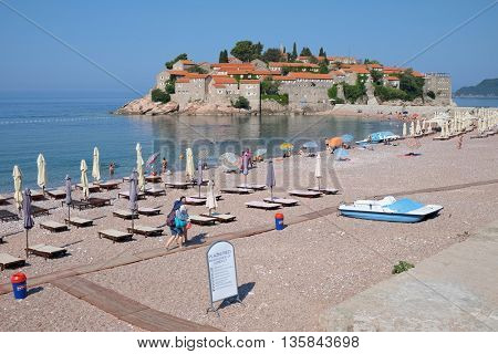 SVETI STEFAN, MONTENEGRO - JULY 08, 2015: deckchairs and beach umbrellas on seashore in front of Sveti Stefan. The shot frames the beautiful landscape of sea and island of Sveti Stefan