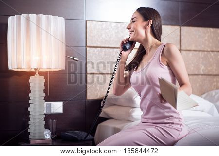Lest ask them. Beautiful excited young woman sitting on the bed in the hotel and calling to the service