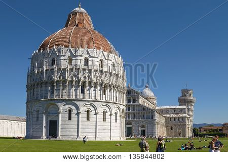 Pisa, Italy - September 29, 2010: Tourists Enjoying Sunny Day In Front Of Baptistery At Leaning Towe