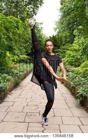 A Jazz dancer performing a kick outdoors