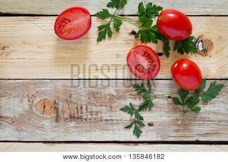 Fresh Organic Tomatoes With Green Leaves On A Wooden Background, Top View.