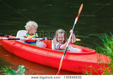 Family on kayak and canoe tour. Two little kids paddling in kayaks in a river on a sunny day. Children in summer sport camp. Active preschoolers kayaking in a lake. Water fun during school vacation.