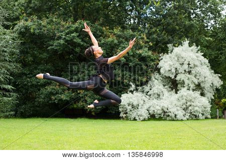 A jazz dancer performing a jump outdoors