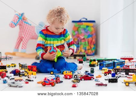 Funny curly toddler boy playing with his model car collection on the floor. Transportation and rescue toys for children. Toy mess in child room. Many cars for little boys. Educational games for kids.