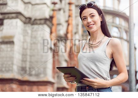 Contemporary world. Pleasant beautiful delighted woman holding tablet and looking aside while standing in the street