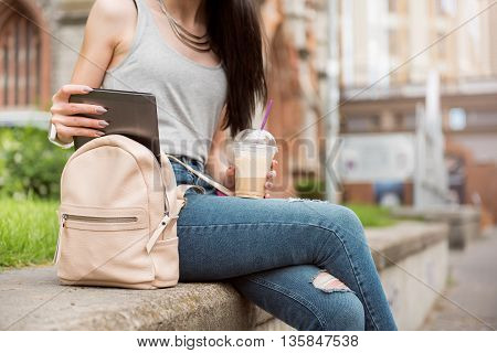 Get some rest. Pleasant woman drinking coffee and holding tablet while resting outside in the street
