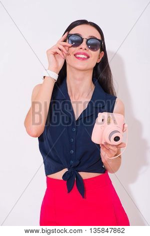 Live bright. Cheerful delighted smiling woman holding photo camera and expressing joy while standing isolated on white background