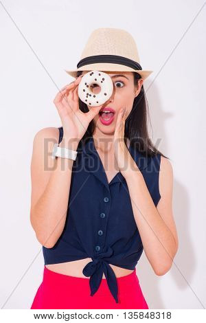 Emotional moment. Positive delighted charming woman holding donut and going to eat it while expressing wonder