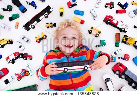 Funny curly toddler boy playing with his model car collection lying on the floor. Transportation and rescue toys for children. Toy mess in kids room. View from above. Many cars for little boys.