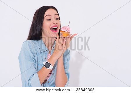 My tasty. Positive emotional cheerful woman holding cupcake and going to eat it while standing isolated on white background