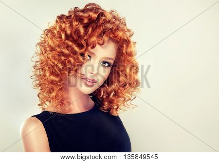 Girl model with long red wavy hair. Big curls on the red head . Hairstyle permanent waving