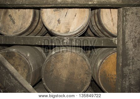 Barrels of Kentucky Bourbon Whiskey aging in a warehouse.