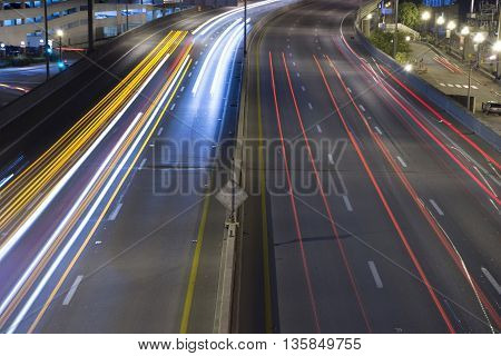 Streaks of lights from headlights and taillights from highway traffic overhead view.