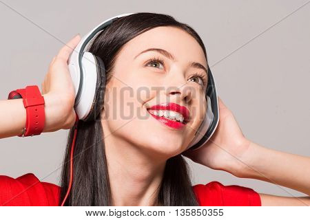 Emotionally charged. Portrait of cheerful delighted smiling woman expressing gladness and listening to music