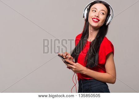 Rest with pleasure. Cheerful delighted beautiful woman smiling and holding cell phone while listening to music