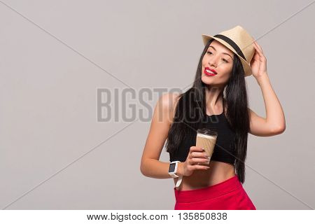 Favorite beverage. Pleasant delighted magnetic woman holding coffee and touching her hat while standing isolated on grey background