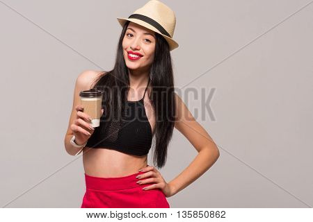 Full of positivity. Pleasant joyful beautiful woman drinking coffee and smiling while standing isolated on grey background