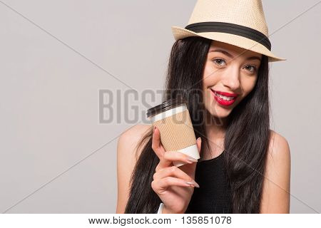 Magic beverage. Pleasant beautiful joyful woman holding coffee and going to drink it while expressing gladness