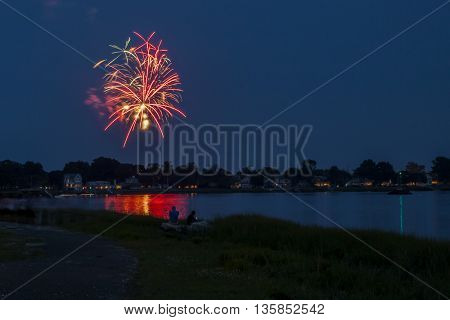 NORWALK, CONNECTICUT - JULY 3: Evening at park near downtown  bridge with people watching for 4th of July fireworks in Norwalk in July 3, 2015 in Norwalk, Connecticut.