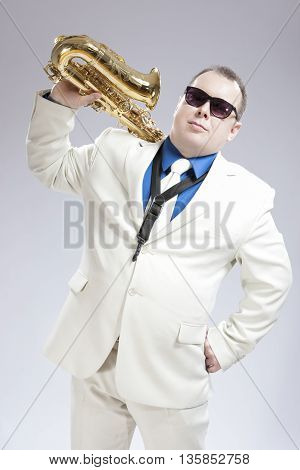 Portrait of Handsome Caucasian Saxophone Player With Music Instrument Over Shoulder. Posing Against White. Vertical Image Orientation