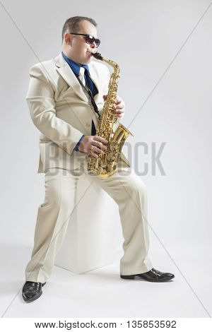 Music Concepts. Handsome Male Saxophone Player Playing in Studio Environment. Wearing Stylish Suit and Sunglasses. Vertical Image Orientation