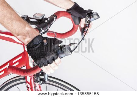 Cyclist Hands in Protective Gloves Put on Handlebars. Pressing Front and Rear Brakes Levers. Against White. Horizontal Image Composition