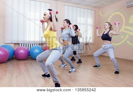 Four Professional Sportswomen Having Trunk Bending Exercises with Barbells. In Sport Class with Fitballs Around. Horizontal Image