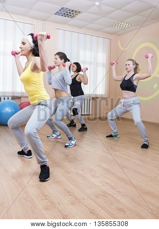 Sport and Fitness Concepts. Four Professional Sportswomen Having Trunk Bending Exercises with Barbells. Training In Sport Class. Vertical Image Composition
