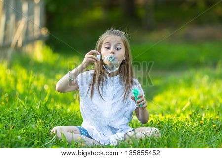 Little girl blowing bubbles sitting on the grass.
