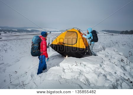Two lady hikers setting up yellow tent in the winter snow field