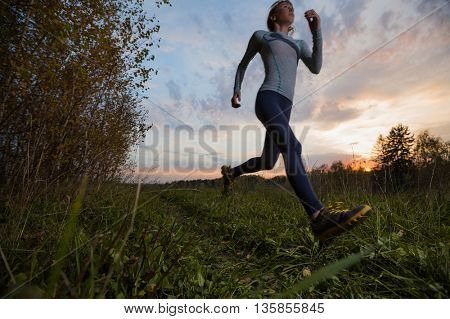 Slim woman running in the autumn forest