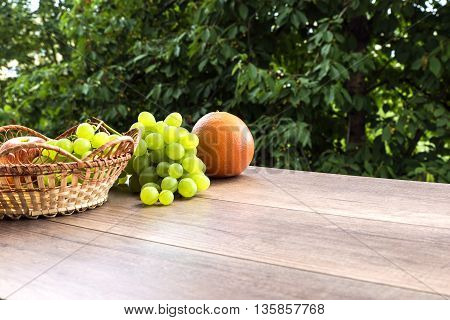 wicker basket with fresh fruit on a wooden table, on a summer morning