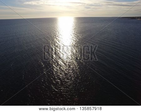 This is a picture on Nantucket Sound in December. The ocean and very calm because there is no wind and the sun is slowly starting to set. The sun is creating a beautiful reflection on the water. This picture is breathtaking.