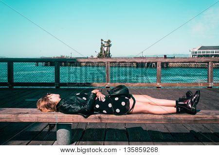 Girl Lying Down On A Bench At San Francisco, California