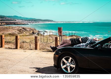 Girl On Top Of Convertible At Half Moon Bay, California