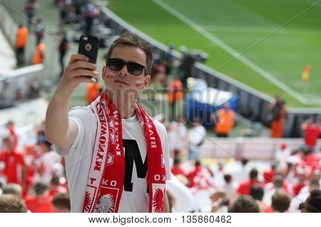 MARSEILLE FRANCE - JUNE 21 2016: Polish fan makes selfie portrait on the smartphone during the UEFA EURO 2016 game Ukraine v Poland at Stade Velodrome in Marseille