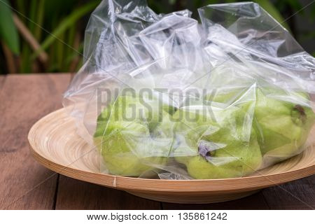 Guava in plastic bag and the bamboo plate.