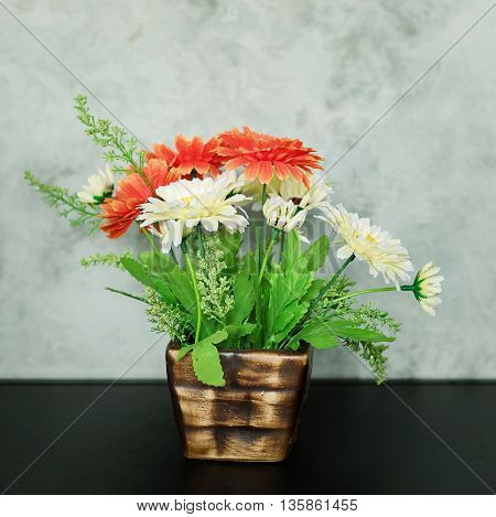 artificial flowers in flowerpot and white wall
